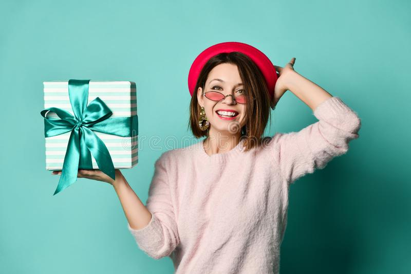 Photo of beautiful woman in felt hat holding present gift box royalty free stock photo