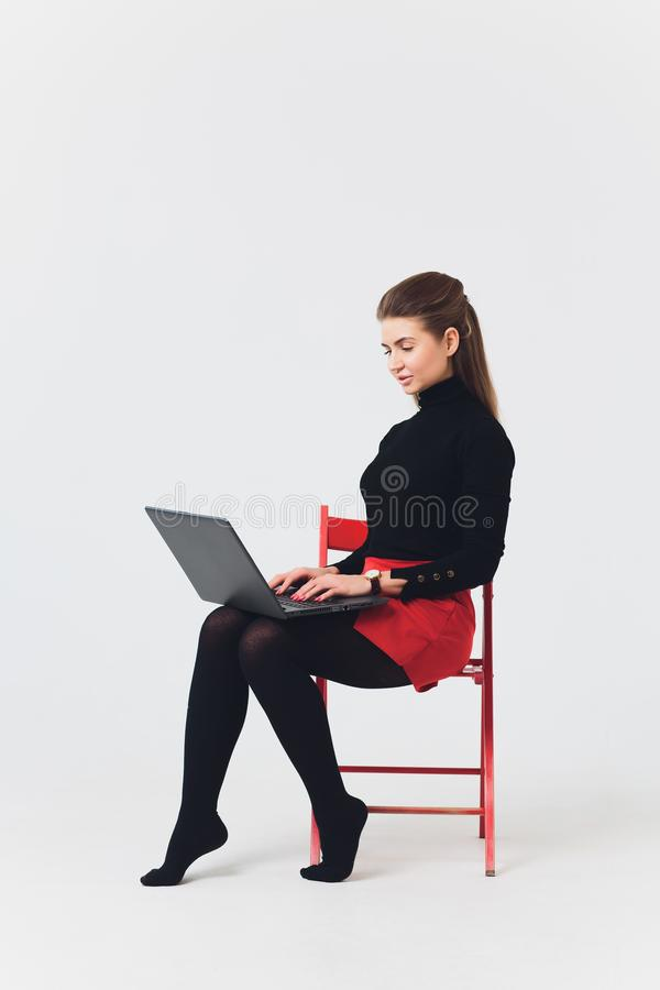 Photo of beautiful woman 20s smiling and using computer with legs crossed isolated over white background. royalty free stock photo