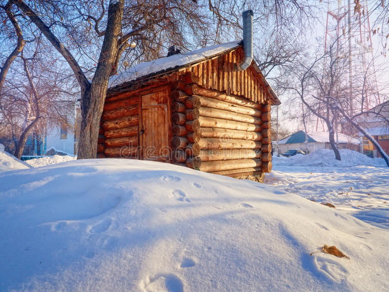 Photo of beautiful wooden outhouse with roof under the snow. A photo of a beautiful wooden outhouse with a roof under the snow stock images