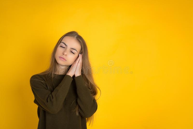 Photo of beautiful young cute woman posing isolated over yellow background sleeping. stock image