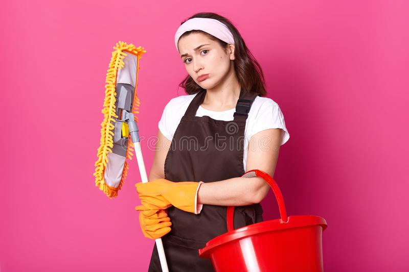 Photo of beautiful young housewife with pouty lips, does not want to clean her house instead of going for dating, being upset with royalty free stock photography