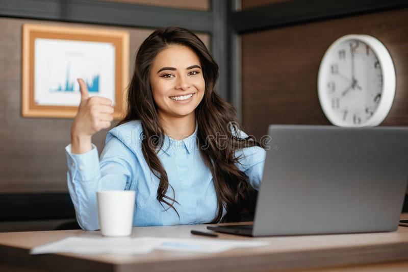 Photo of beautiful young manager woman working with laptop and show good gesture in modern office. royalty free stock photo