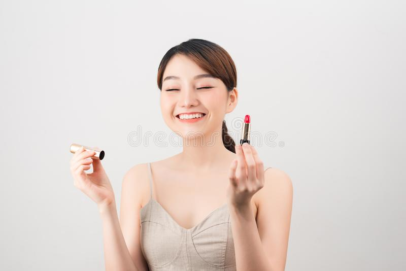 Photo of a beautiful young pretty asian woman with healthy skin posing naked isolated over white wall background holding lipstick royalty free stock photos