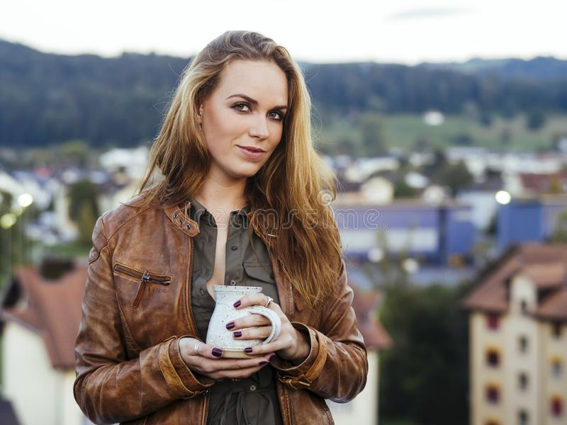 Beautiful young woman drinking coffee outdoors. Photo of a beautiful young woman drinking coffee outdoors with village in the background stock image