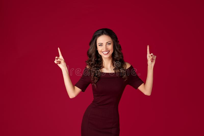 Photo of beautiful young woman in maroon dress point fingers up over red background. Photo of beautiful young woman in maroon dress point fingers up over red stock photo