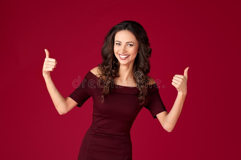 Photo of beautiful young woman in maroon dress show ok gesture over red background. Photo of beautiful young woman in maroon dress show ok gesture over red royalty free stock image