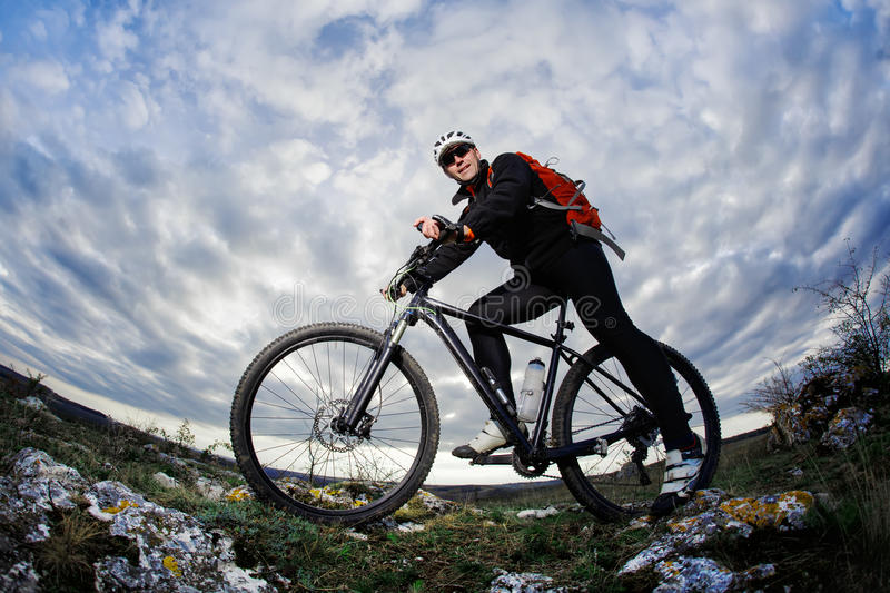 Photo below of the mountain cyclist in the black sportwear on the rocks against dramatic sky with clouds. royalty free stock photography