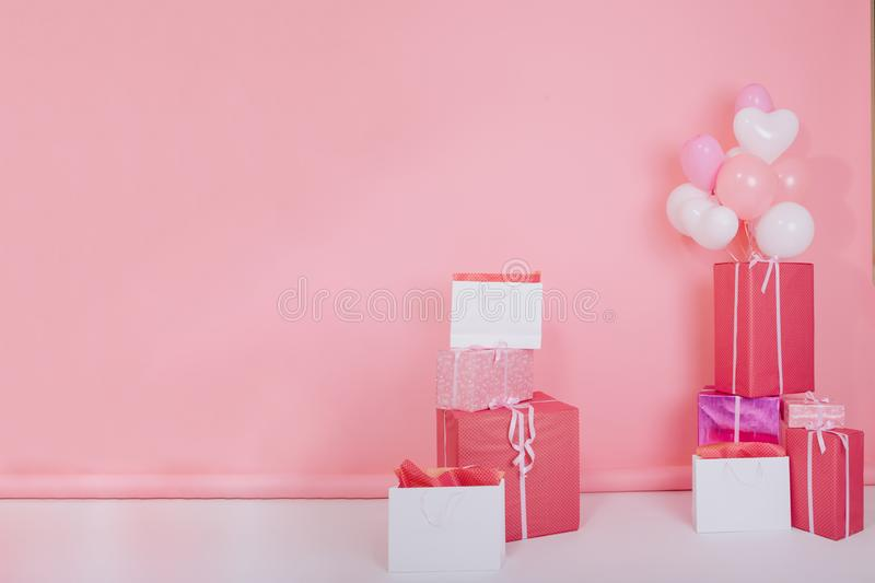 Photo of big bright presents and white party balloons for birthday standing on the floor. Colorful gift boxes with cute. Ribbons for christmas or st. valentines stock photography