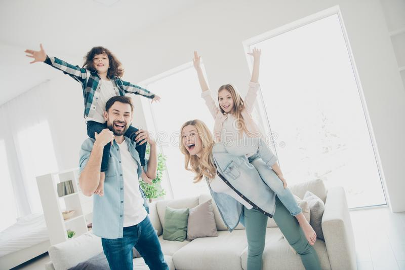 Photo of big family four members having best free time hands raised up pretend airplane flight indoors apartments royalty free stock photo