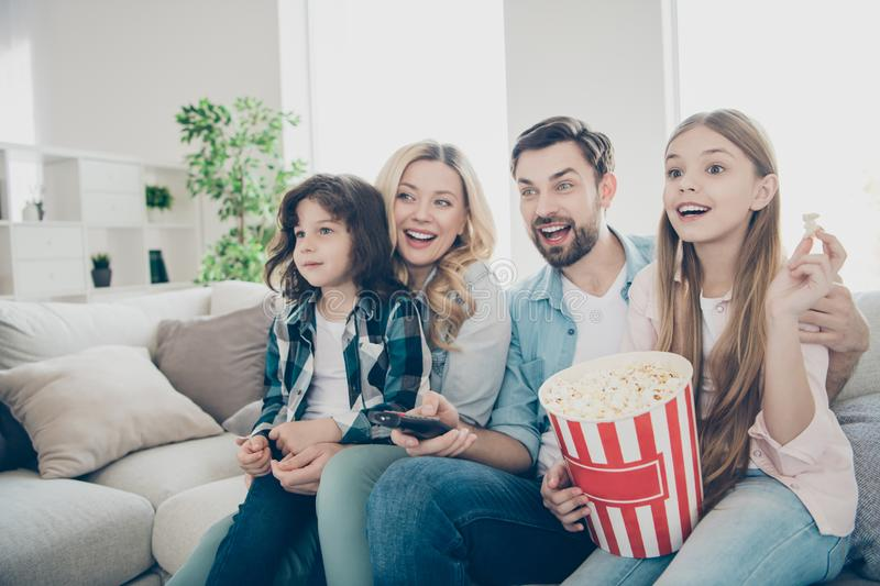 Photo of big family four members spend leisure time by watching tv show sit couch eat salty popcorn. Photo of big family four,members spend leisure time by stock photos