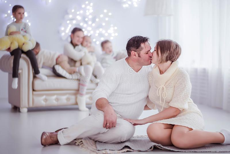 Big family in a New Year s interior. Husband and wife are looking at each other and kissing royalty free stock photography