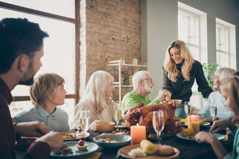 Photo of big full family reunion gathering sit feast dishes dinner table young wife giving old parents fresh bakery stock image