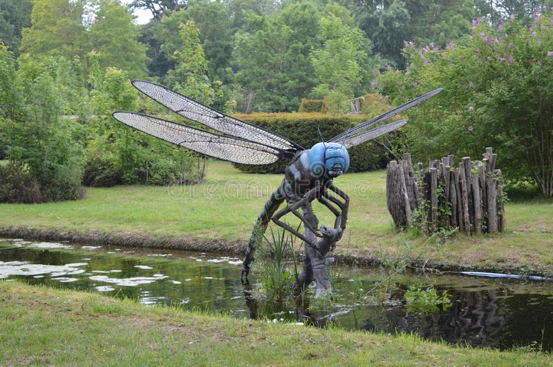 Big model of Dragonfly in black and blue colors. Photo of big model of Dragonfly in black and blue colors above the little river in park royalty free stock images