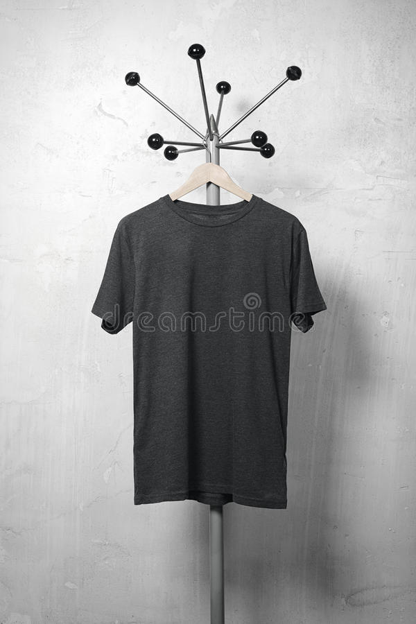Photo of black blank tshirt hanging on the hanger. Vertical royalty free stock image