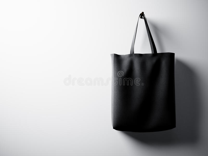 Photo black cotton textile bag hanging right side. Empty white wall background. Highly detailed texture, space for. Photo black cotton textile bag hanging right stock photo