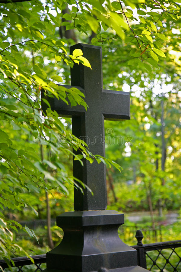 The photo of the black stone of the Christian cross on a background of sunlit abundant forest-Park greenery of trees, shrubs and. The photo of the black stone of royalty free stock photos