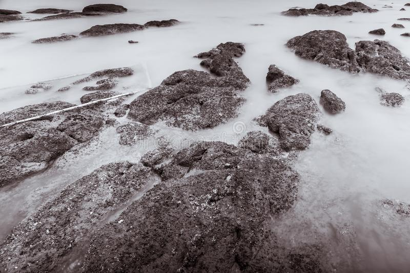 Photo Black and White of Long Exposure Photography Waves on stone beach waters edge abstract sea background.Thailand. Blue, blur, break, capture, close-up stock photography