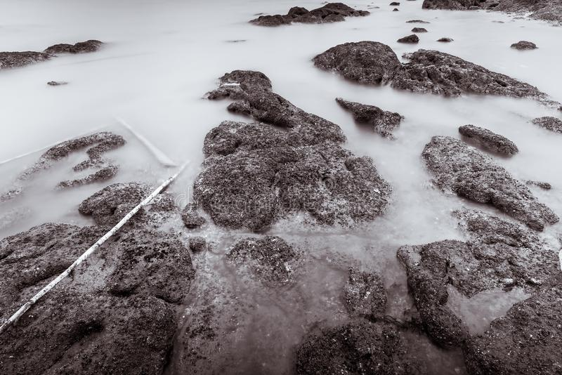 Photo Black and White of Long Exposure Photography Waves on stone beach waters edge abstract sea background.Thailand. Blue, blur, break, capture, close-up royalty free stock image