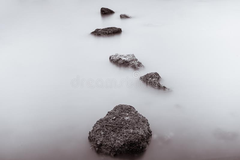 Photo Black and White of Long Exposure Photography Waves on stone beach waters edge abstract sea background.Thailand. Blue, blur, break, capture, close-up stock images