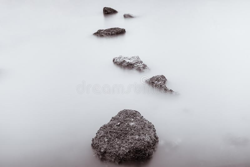 Photo Black and White of Long Exposure Photography Waves on stone beach waters edge abstract sea background.Thailand. Blue, blur, break, capture, close-up royalty free stock photo