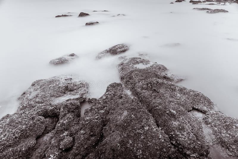 Photo Black and White of Long Exposure Photography Waves on stone beach waters edge abstract sea background.Thailand. Blue, blur, break, capture, close-up royalty free stock images