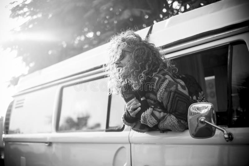 Photo in black and white of woman smiling very happy in the window of a beautiful and old van - adult with sunglasses having fun royalty free stock photo