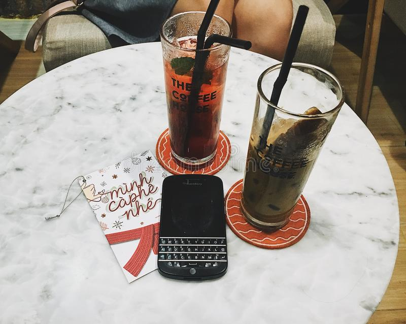 Photo of Blackberry Phone Beside Two Tall Glasses royalty free stock photo
