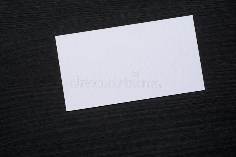 Photo of blank white business cards on a dark wooden background. Mock-up for branding identity. stock photos