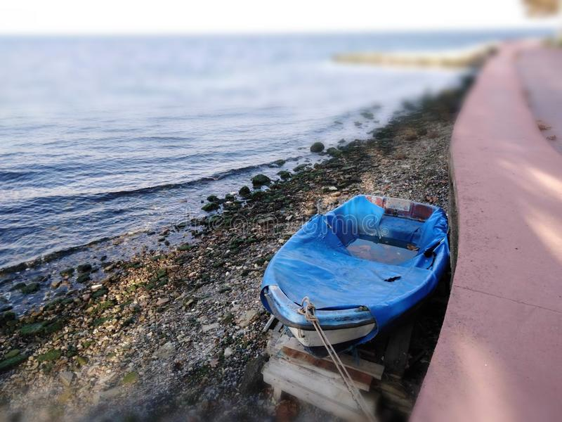 A photo of blue boat. A blue boat full of water beside of Pink seaway after the Rain. beach rocks fishing photo stock image