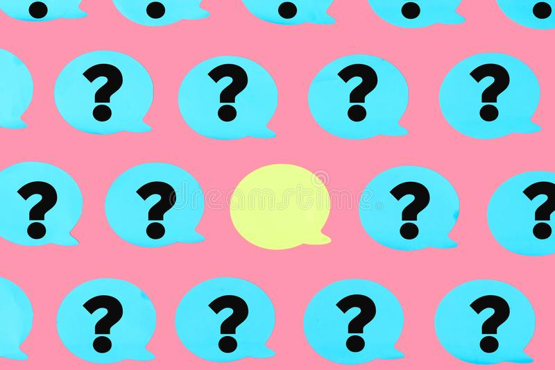 Photo, blue stickers with question marks on a pink background. In the center is an empty yellow sticker. A bright stock illustration
