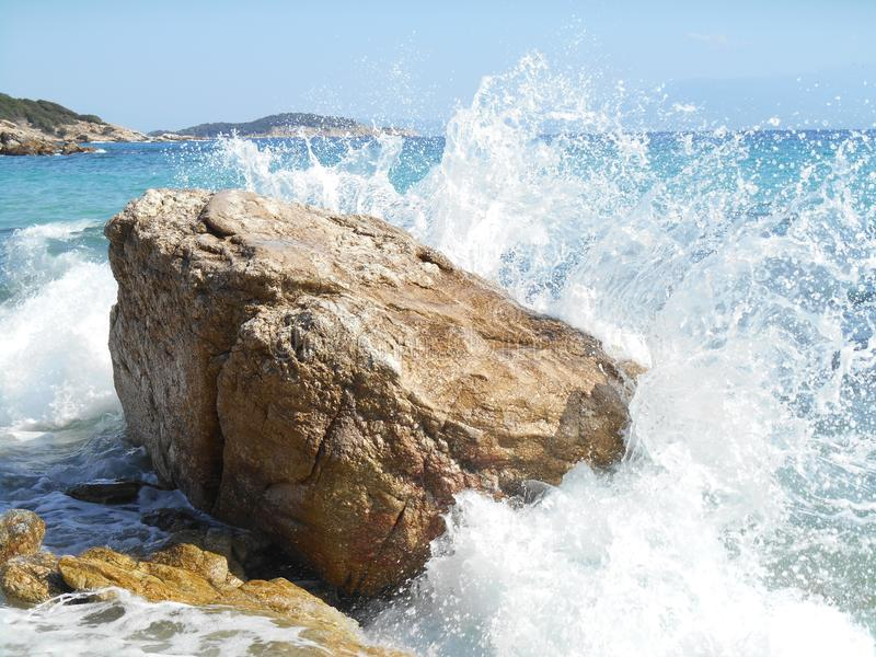 Sea waves going into big rock. Photo of blue and white sea waves going into big brown rock, bright blue sky and mountains in background stock photos