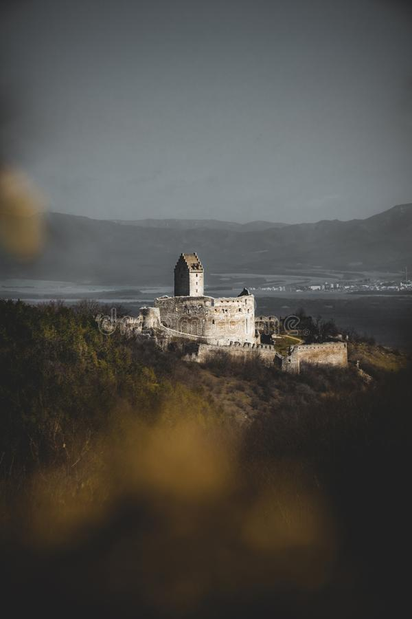 Photo through the bluerred yellow leafs of Illuminated castle with wall on right side in Slovakia - Europe Podhradie. Image of r. Uins with village on background stock images