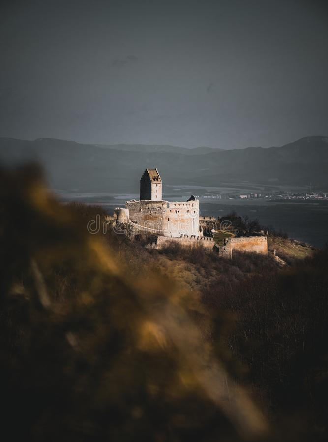 Photo through the bluerred yellow leafs of Illuminated castle with wall on right side in Slovakia - Europe Podhradie. Image of r. Uins with village on background stock photo