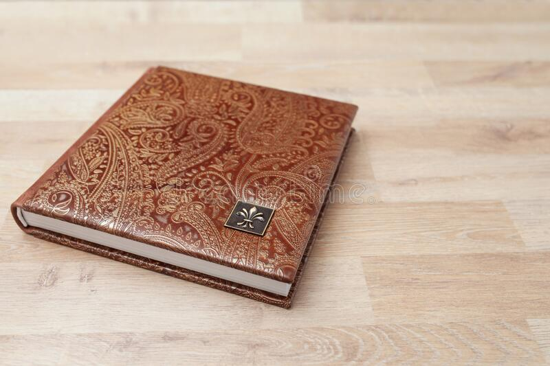 Photo book, notebook or diary with a cover of genuine leather. Brown color with decorative stamping. Wedding or family photo album royalty free stock images