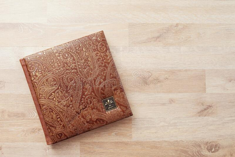 Photo book, notebook or diary with a cover of genuine leather. Brown color with decorative stamping. Wedding or family photo album stock images