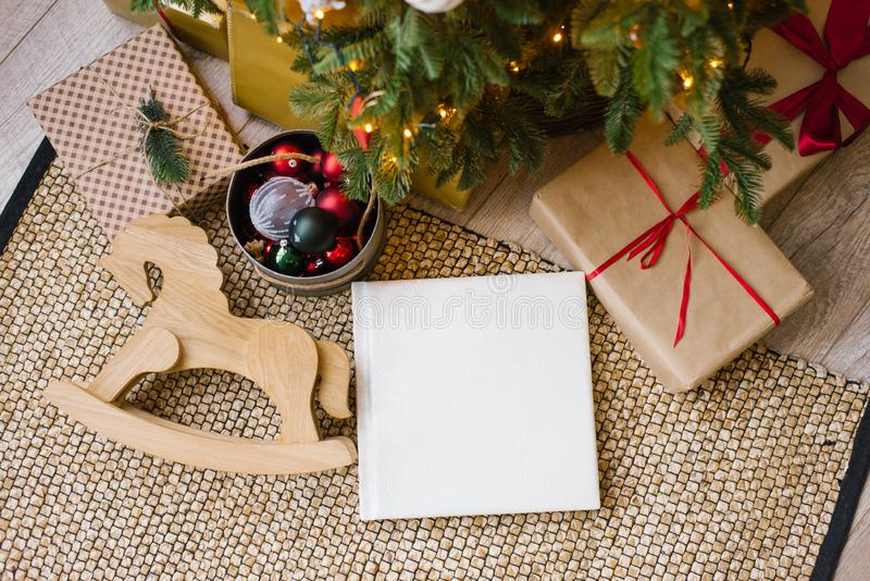 Photo book in white leather cover, wedding or family photo album under the Christmas tree surrounded. By Christmas gifts royalty free stock image