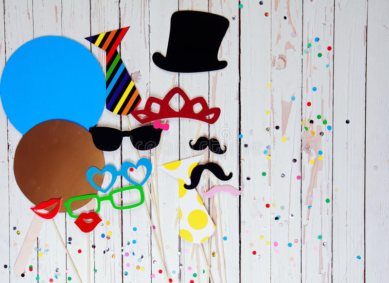 Photo booth accessory background. With colorful paper fashion accessories, lips, and moustaches on white wooden background sprinkled with multicolored party royalty free illustration