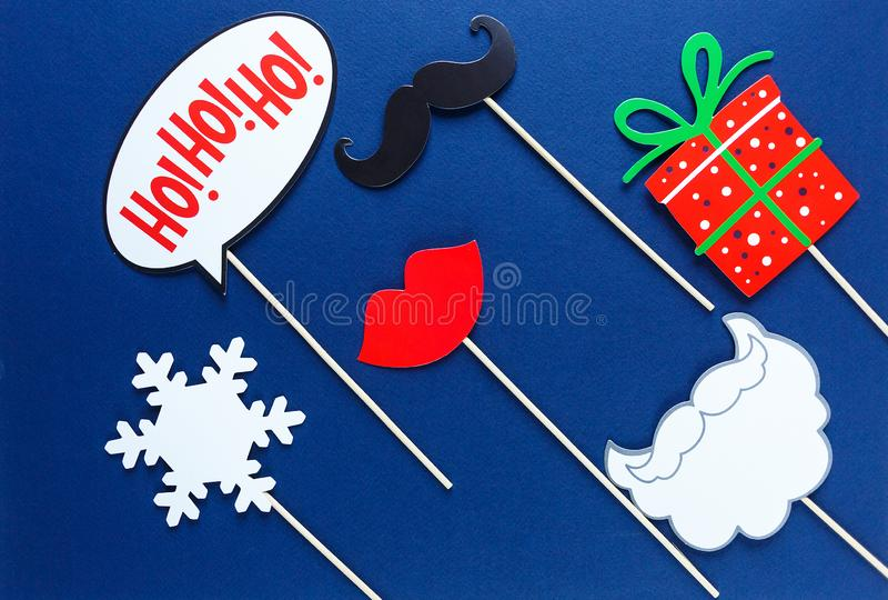 Photo booth colorful props for christmas party - red lips, snowflake, gift, moustache on blue background. Christmas and New year decorations stock photo