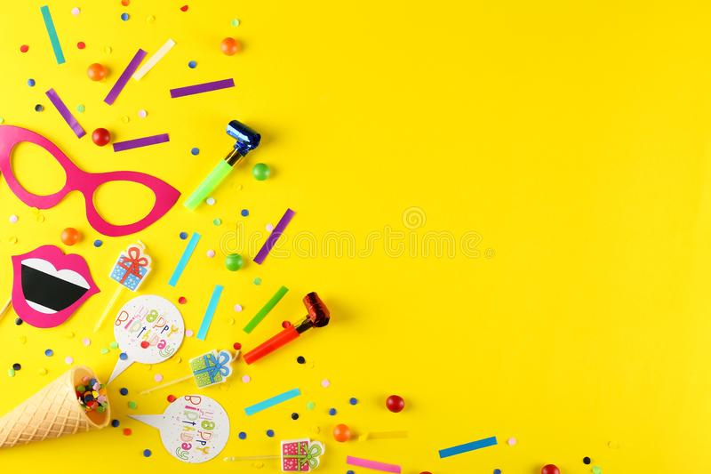 Birthday party kit with copy space. Photo booth props and party horns on yellow background. Paper moustache, lips and glasses on stick. Party kit for birthday stock photography