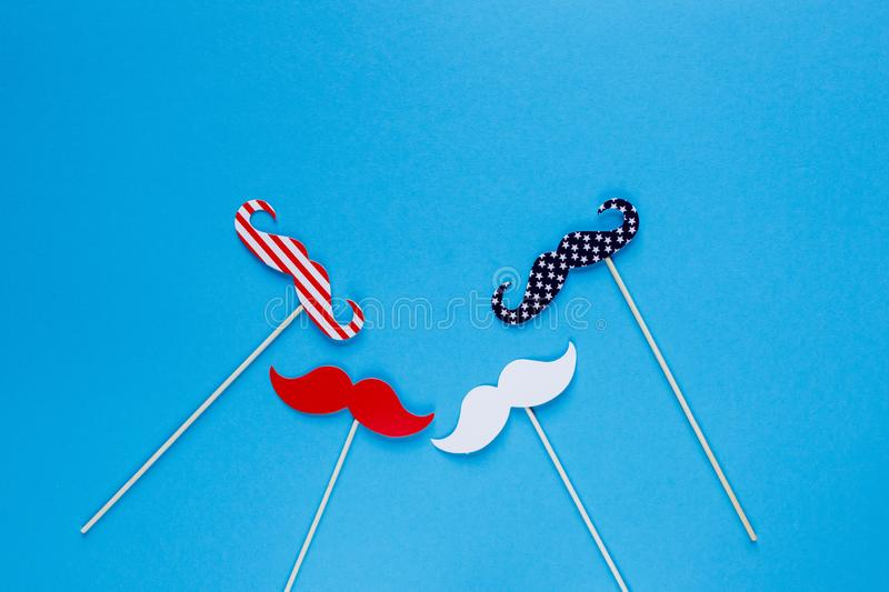 Photo booth for 4th of July. Moustache on sticks on blue background. American flag colors. Independence Day royalty free stock photos