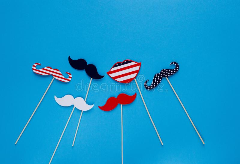 Photo booth for 4th of July. Moustache on sticks on blue background. American flag colors. Independence Day royalty free stock images
