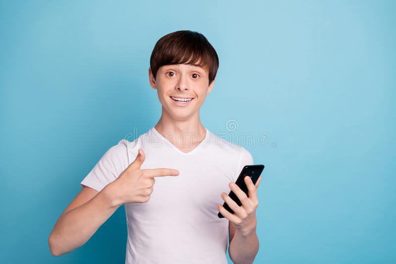 Photo of boy having been told to sell phone he is pointing at while isolated with blue background stock photography