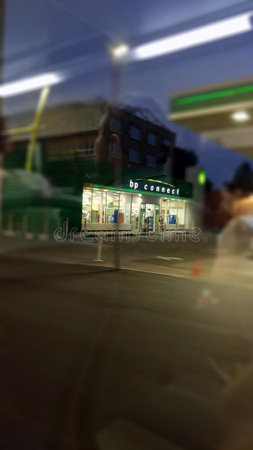 Photo of a bp connect station from a bus window. Picture of an evening view of bp connect station from a bus window stock photo