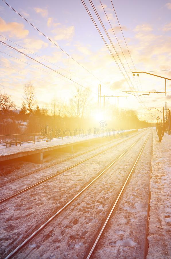 Photo of bright and beautiful sunset on a cloudy sky in cold winter season. Railway track with platforms for waiting trains and p stock image