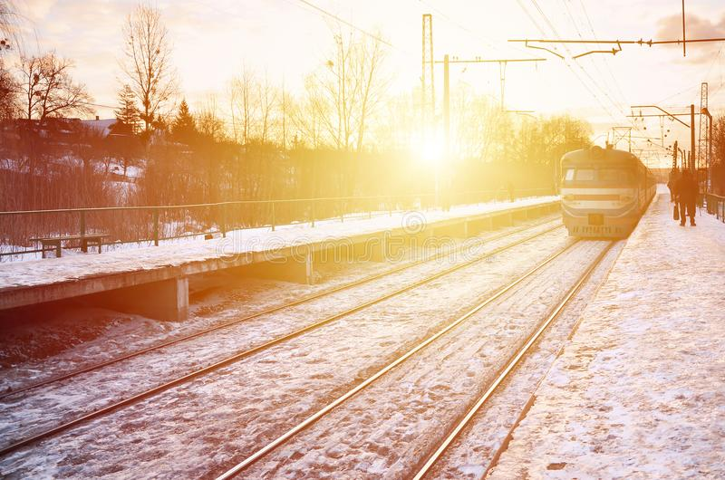 Photo of bright and beautiful sunset on a cloudy sky in cold winter season. Railway track with platforms for waiting trains and p royalty free stock photography