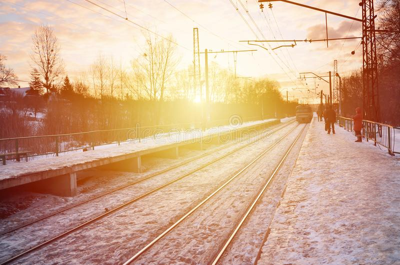 Photo of bright and beautiful sunset on a cloudy sky in cold winter season. Railway track with platforms for waiting trains and p stock images
