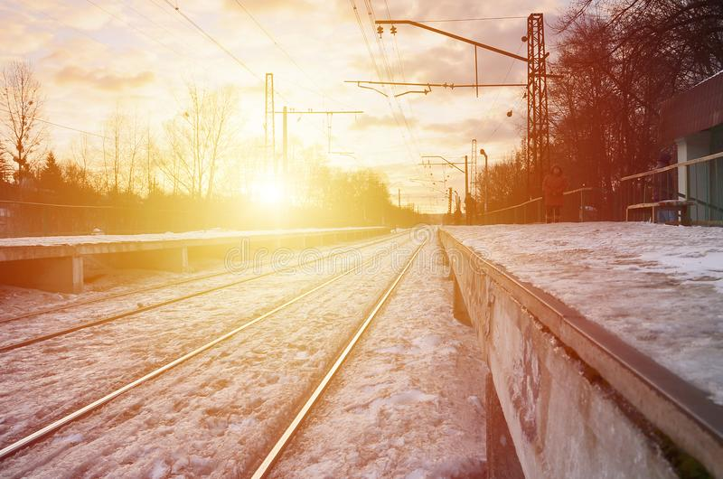 Photo of bright and beautiful sunset on a cloudy sky in cold winter season. Railway track with platforms for waiting trains and p stock photography