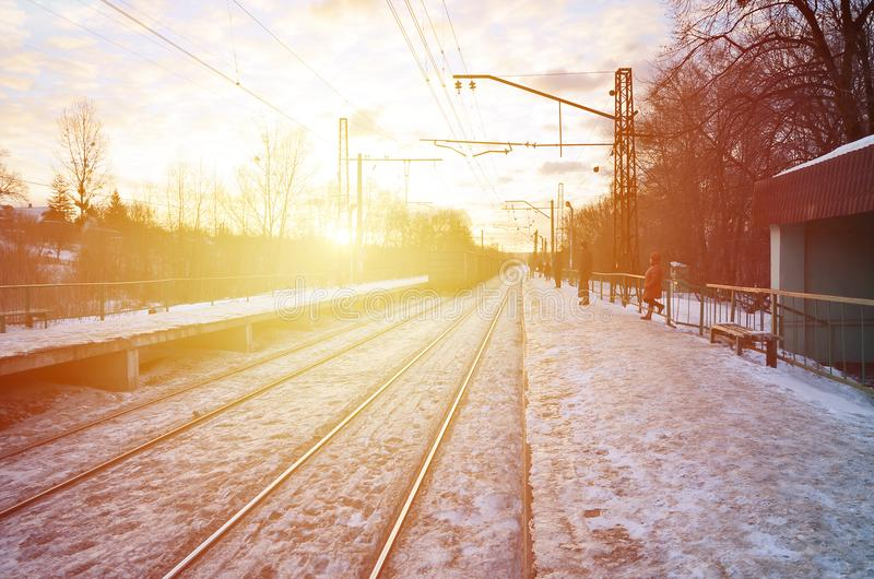 Photo of bright and beautiful sunset on a cloudy sky in cold winter season. Railway track with platforms for waiting trains and p royalty free stock images