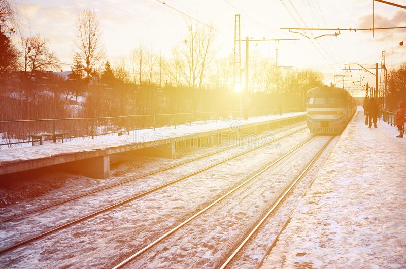 Photo of bright and beautiful sunset on a cloudy sky in cold winter season. Railway track with platforms for waiting trains and p royalty free stock photos
