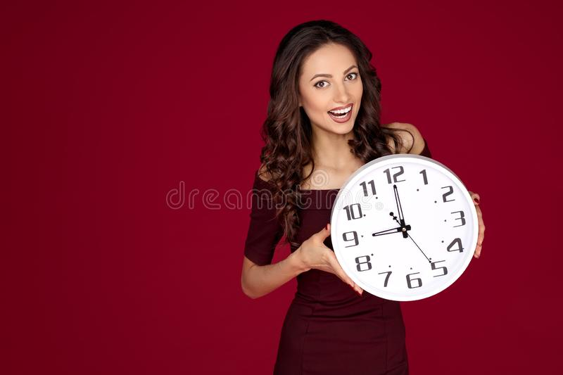 Photo of bright young modern business woman in maroon dress holding a clock over red background,. Photo of bright young modern business woman in maroon dress royalty free stock photography